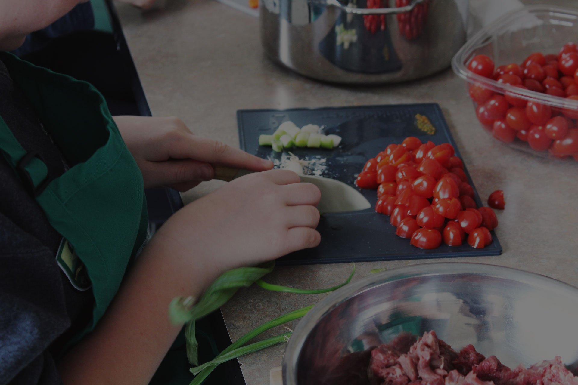 Close up of a child chopping tomatoes and garlic. They wear a green apron. A black filter darkens the image.