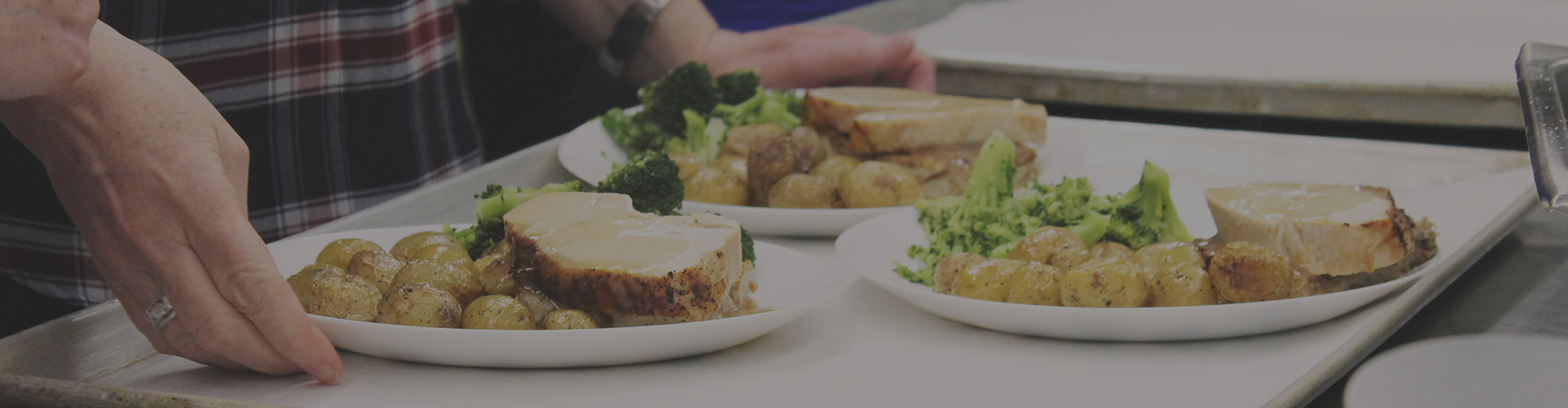 Close up of someone holding a tray bearing three plates of meat, broccoli, and potatoes. A line of other people and trays can be seen out of focus and lined up next to this person. A black filter darkens the image.