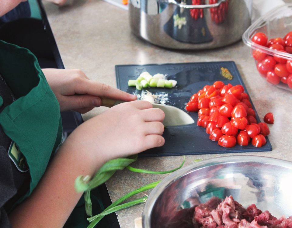 Close up of a child chopping tomatoes and garlic. They wear a green apron.