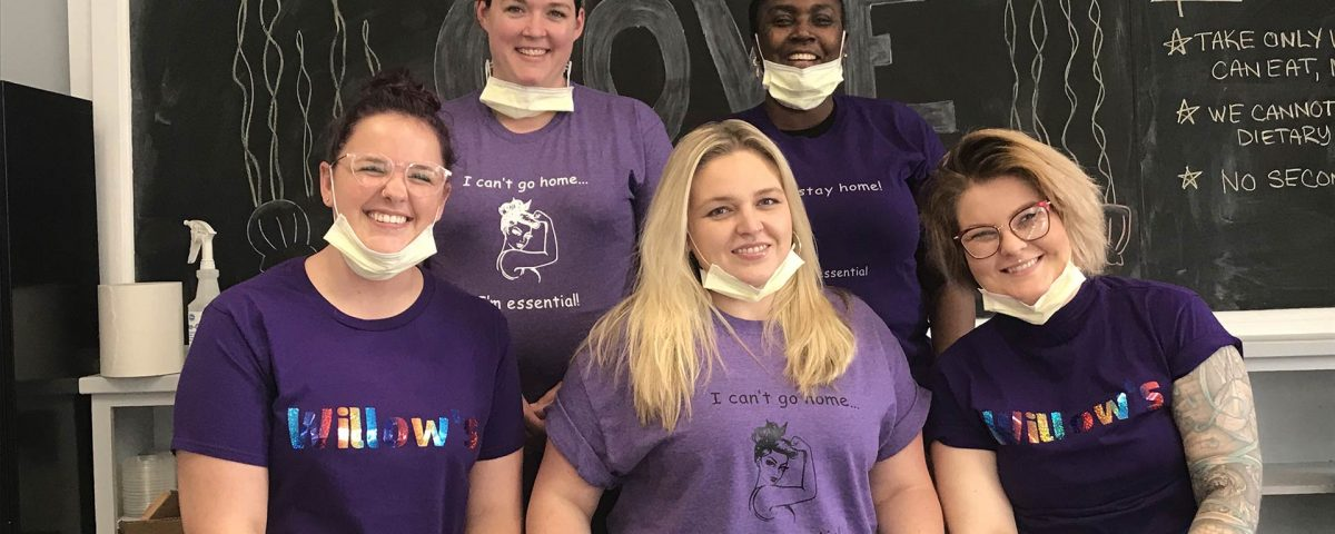 Five women wearing purple shirts and face masks pulled down on their faces smile at the camera. They stand in front of a chalkboard.
