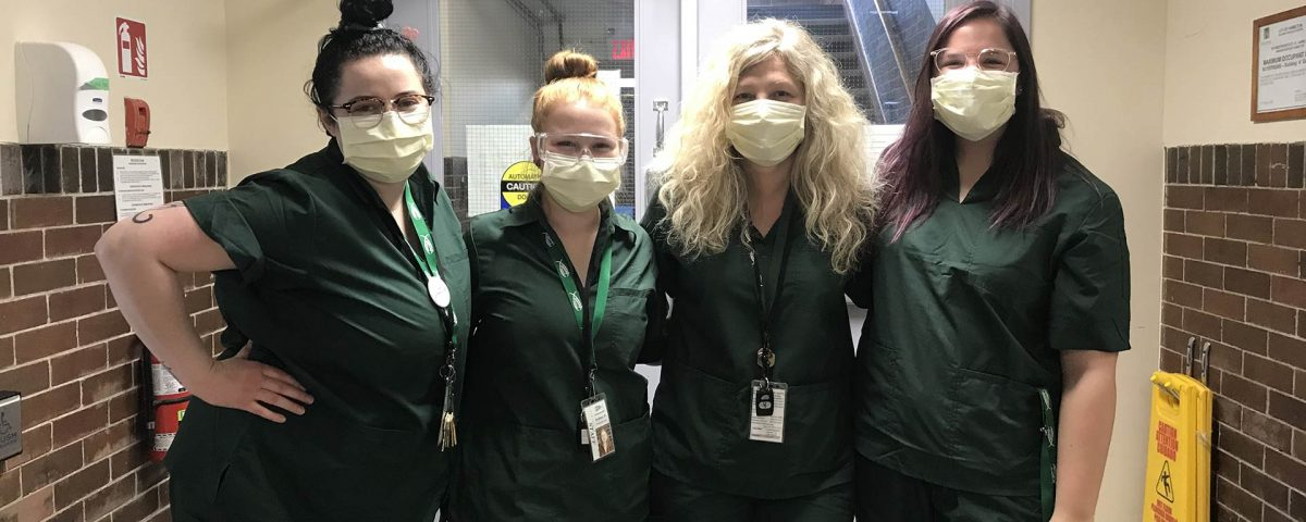 Four women wearing green scrubs and face masks stand in a hallway with their arms around each other.