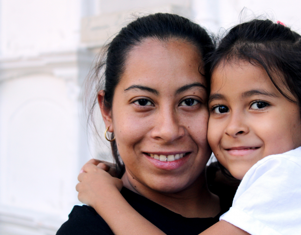 A woman wit dark hair looks at the camera and holds her young daughter, who is smiling.