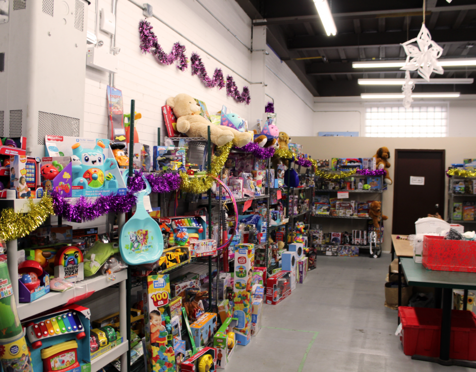 The Gift Room is a warehouse room filled with colourful toys stacked on shelves. The room is decorated with Christmas decorations.