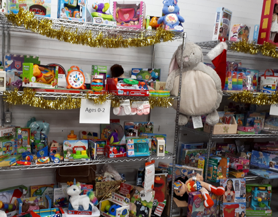Warehouse gift room with shelves filled with colourful toys for young children.
