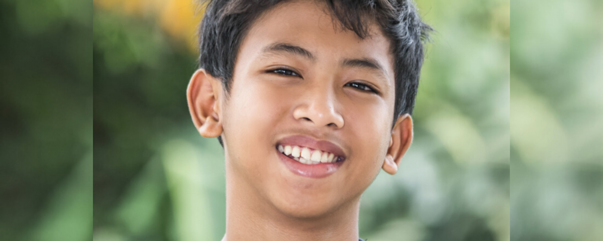 An adolescent boy with brown skin and dark hair smiles at the camera. He stands in front of a blurred leafy background.