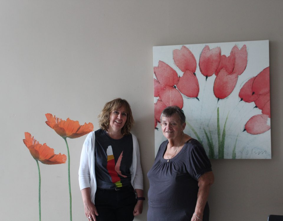 Two women, one older than the other, stand in front of a large floral painting and smile at the camera.