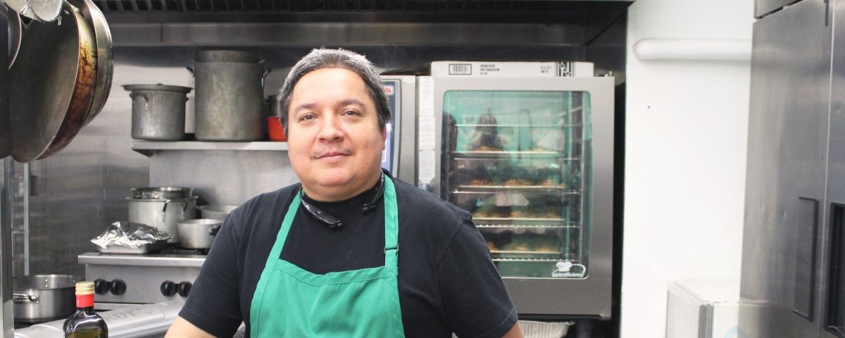 Man wearing a green Mission Services apron and hairnet, standing in an industrial kitchen. He smiles at the camera.