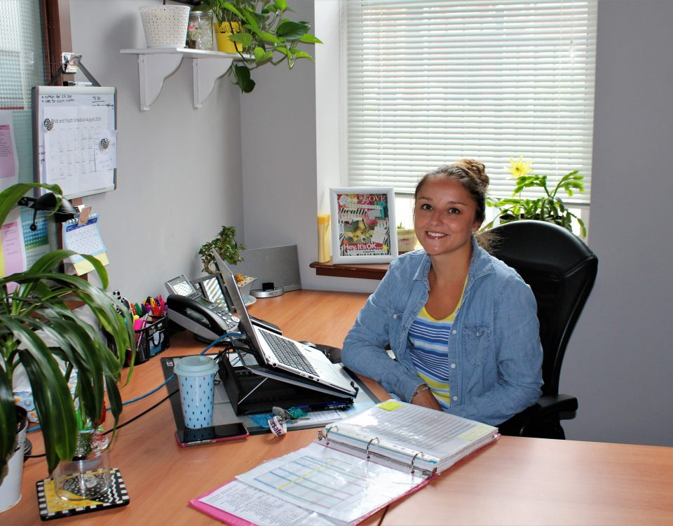 A young woman sits at a desk with plants, a binder, and a telephone. She smiles at the camera.