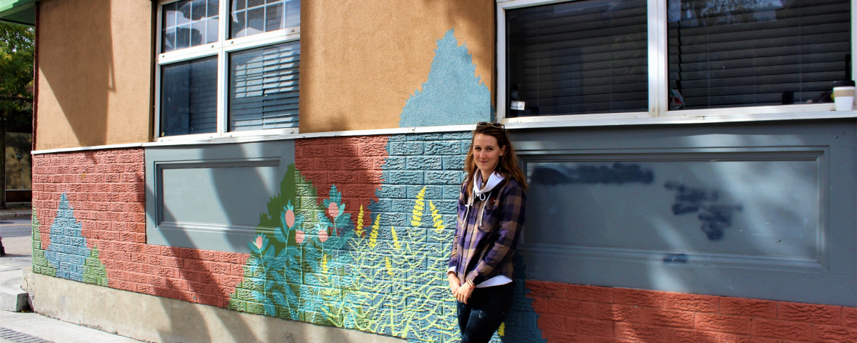 A woman wearing a hooded jacket leans against a brick wall which is painted with a mural of trees and flowers.