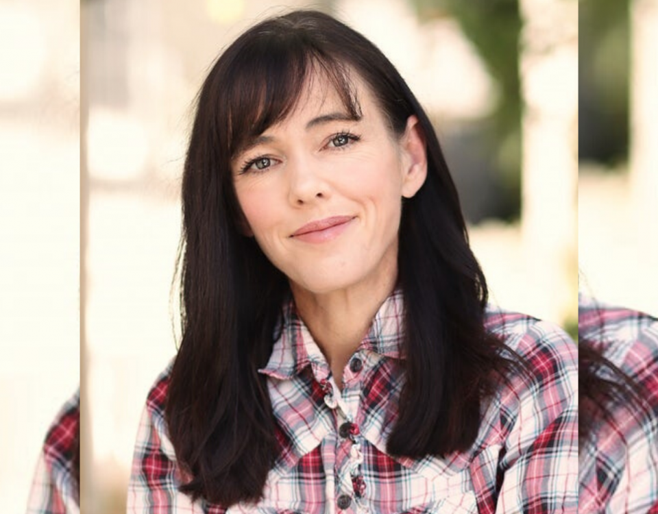 A woman with dark hair and wearing a pink plaid shirt smiles at the camera.