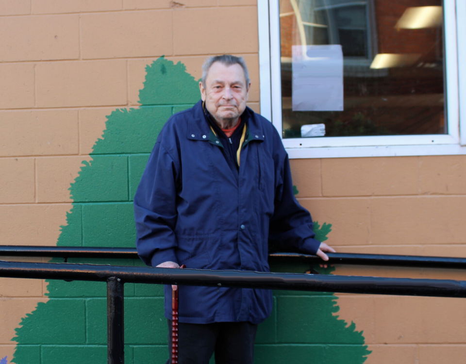 An older man wearing a blue jacket stands on a ramp outside a building, holding a cane in one hand and the railing. His right foot is in a cast. The building has murals of a tree on it.