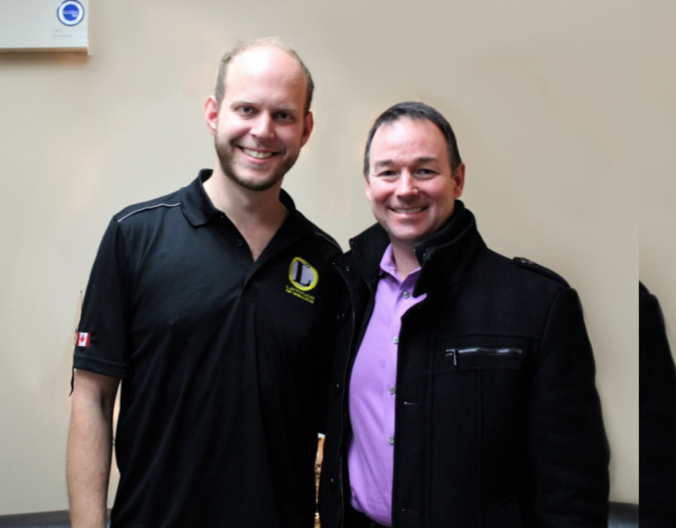 Two white men stand next to each other, wearing black, smiling at the camera.
