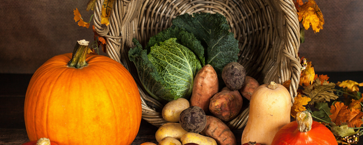 Thanksgiving themed vegetable display with woven basket, pumpkins, colourful leaves, and root vegetables