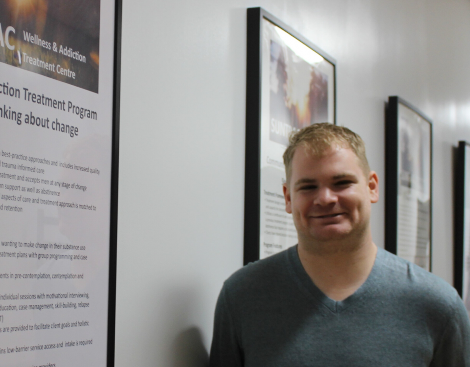 A man with light hair smiles to the camera. He is standing in a hallway with posters describing addiction treatment programs.