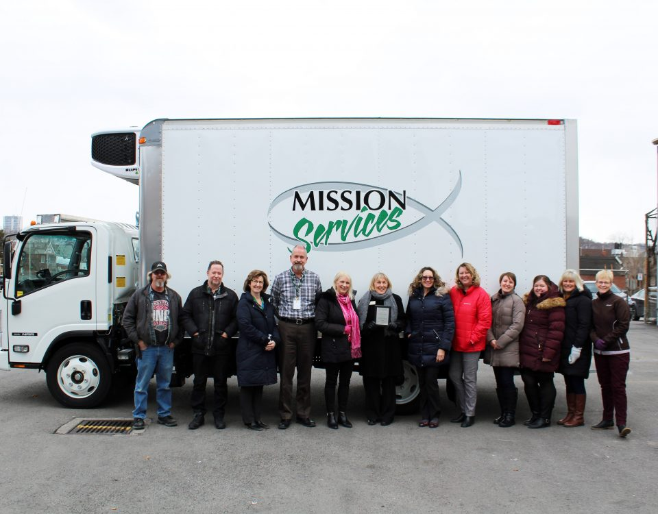 Twelve people wearing winter coats line up in front of a large white refrigerated truck with a Mission Services logo on it.