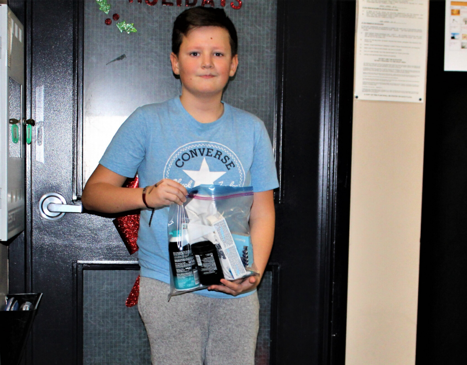 A boy with brown hair stands in front of a closed door, holding up a bag of donated toiletries.