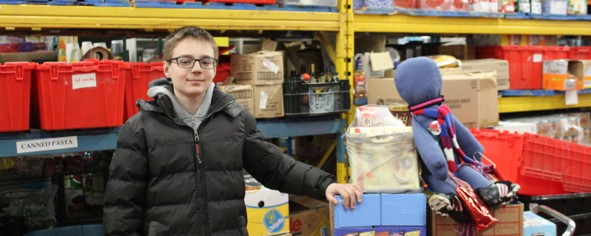 A boy with glasses stands in the warehouse, next to a cart of donations, including a doll.