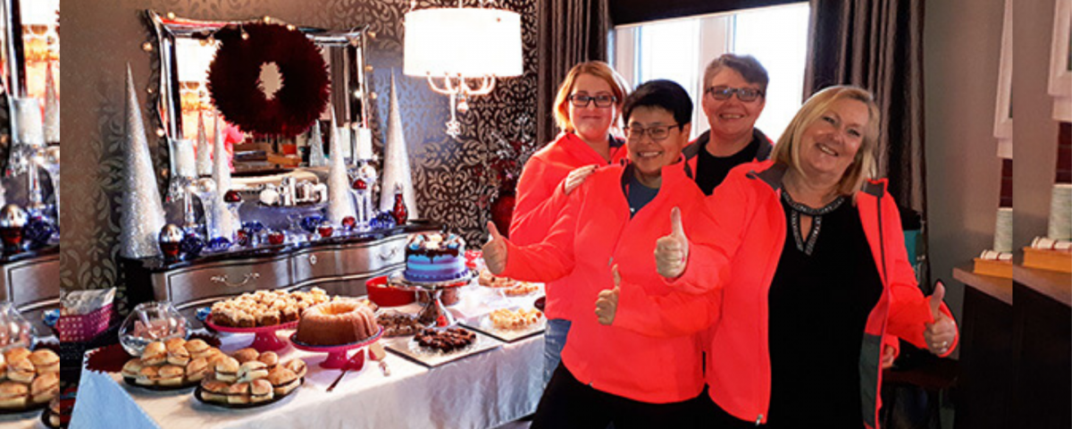 A group of four adults wearing red coats stand in front of a table of holiday food. They are smiling and giving thumbs up to the camera.