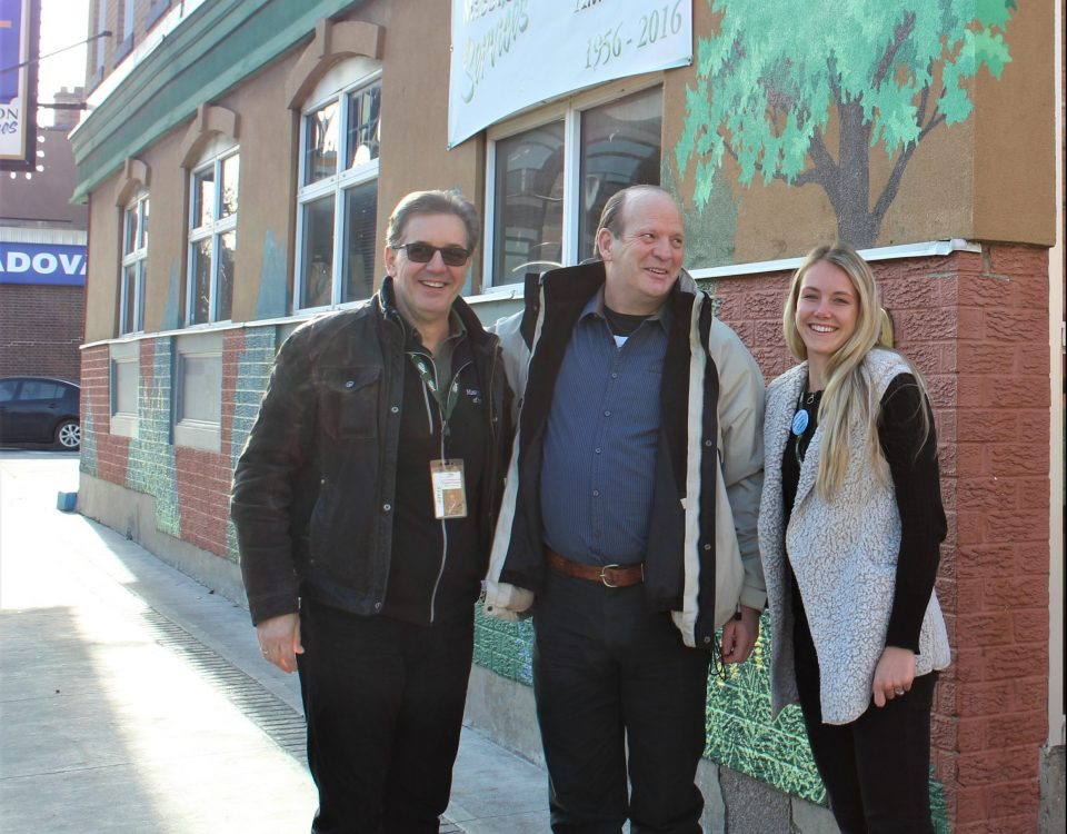 Two white men and a young white woman stand next to each other, laughing and wearing winter coats. They stand in front of the tree mural on the wall of the Men's Shelter on James St N. It's sunny outside.