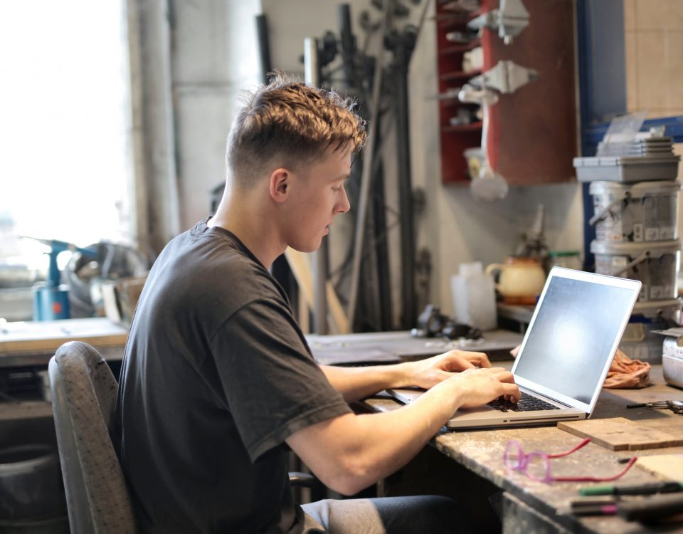 Young white man wearing a t-shirt sits in front of a laptop at a desk in a workshop.