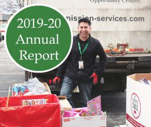 A man with dark hair smiles at the camera and stands in front of a large white Mission Services truck. A number of large boxes filled with donations of Christmas toys fill the space between the man and the camera. A green circle with white text inside reads: 2019-20, Annual Report