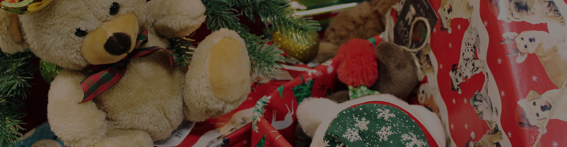 Close up of a teddy bear wearing a bow tie sitting among other Christmas gifts