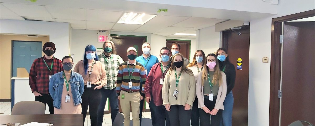 A group of 12 masked people stand in a group, wearing Mission Services lanyards and standing inside a lobby area.