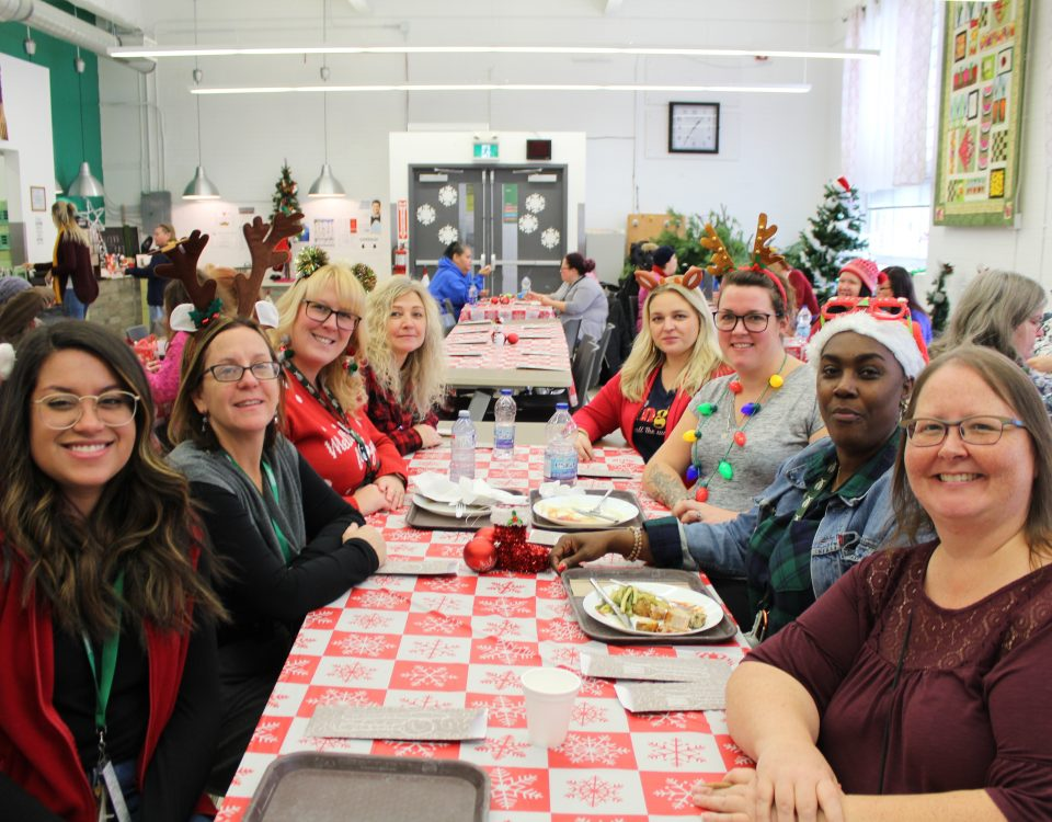 A group of women wearing sweaters and Christmas paraphernalia sit at a table with a Christmas table cloth. They turn to smile at the camera.