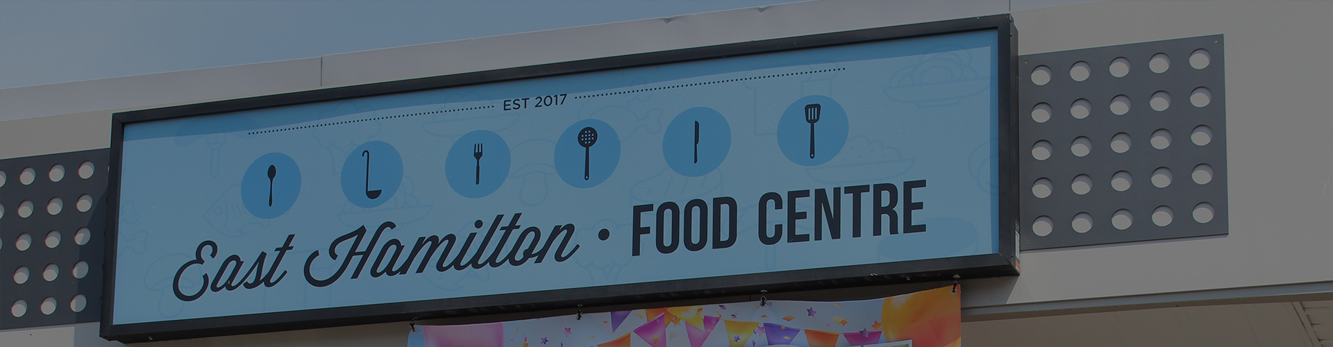 "Photo of a large blue sign that reads ""East Hamilton Food Centre."""