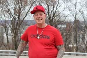 A man wearing a red t-shirt, a red baseball hat, a silver necklance, and with tattoos on both arms smiles at the camera. He stands in front of bare trees. You can see the Hamilton skyline behind the trees.