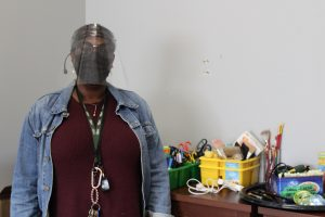 A woman wearing PPE and a denim jacket stands in front of a table with craft supplies.