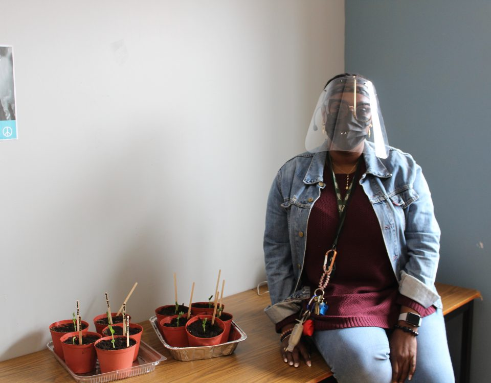 A woman wearing PPE and a denim jacket sits on a table next to several pots of growing plants.