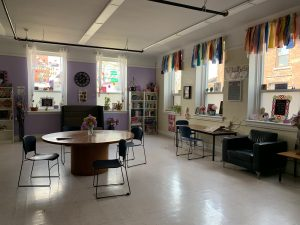 A room with tables, chairs, and decorated with art, ribbons, and posters