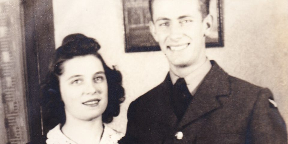 A black and white vintage photo of a young man and woman standing next to each other and smiling at the camera. She wears a dark dress with a white collar, and he wears a dark uniform.